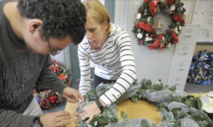 A teacher with a special needs student working on a wreath